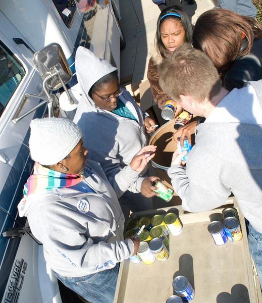 Sasha Edwards, sophomore, Brittany Baird, freshman, Leona Wodston, sophomore, Jaquis Milligan, senior, and Ray Butler, senior, load canned foods onto a cart from donation bags and take inventory for Jam the Bus on Wednesday.