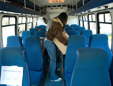 Brittany Baird, freshman, and Leona Wodston, sophomore, pack the bus with food donations in Dede Plaza on Wednesday to support Jam the Bus.