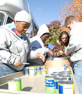 Sasha Edwards, sophomore, Brittany Baird, freshman, Leona Wodston, sophomore, and Ray Butler, senior, load canned foods onto a cart from donation bags and take inventory for Jam the Bus on Wednesday.