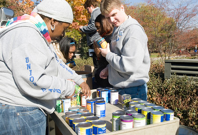 Sasha Edwards, sophomore, and Ray Butler, senior, load canned foods onto a cart from donation bags and take inventory for Jam the Bus on Wednesday.