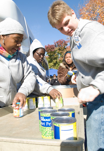 Sasha Edwards, sophomore, Brittany Baird, freshman, and Ray Butler, senior, load canned foods onto a cart from donation bags and take inventory for Jam the Bus on Wednesday.