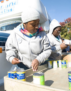 Sasha Edwards, sophomore, and Brittany Baird, freshman, load canned foods onto a cart from donation bags and take inventory for Jam the Bus on Wednesday.