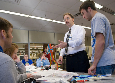 Guest Speaker Raymond G. Amos of Boston Scientific Corp. helps Jaron Powell, Shiann Mathena and Ethan Brewer, all seniors at Linton High School, during the Medical Madness competition.