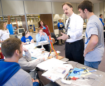 Guest Speaker Raymond G. Amos of Boston Scientific Corp. helps Jaron Powell and Ethan Brewer, both seniors at Linton High School, during the Medical Madness competition.
