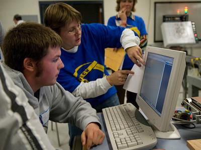 Tonya Lamb assists Blake Vermillion of Area 30 Career center during module of Industrial Robot Programming.