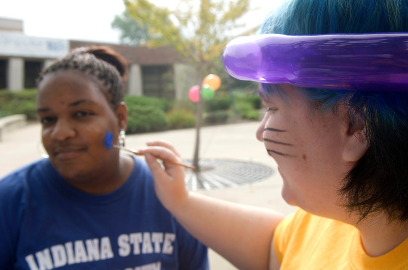 Shadow Endahl, a senior, paints the face of Tiffany Mason, a freshman.
