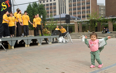 Olivia Hummel, 17 months, dances while a group of theatre students sing at Dede Plaza during Theatre Fest 2007.