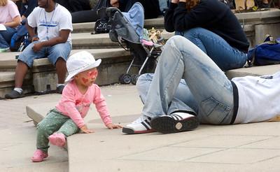 Olivia Hummel, 17 months, observes a resting student during Theatre Fest.