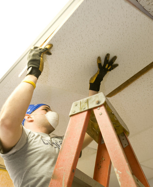 Andrew replaces ceiling tiles at a local church.