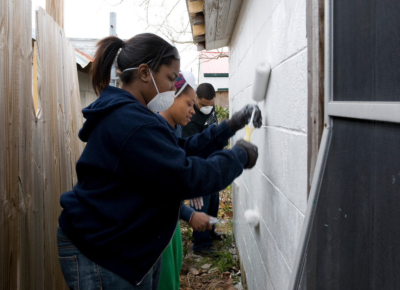 Armelia, Erica and Jeff paint the back side of a house.