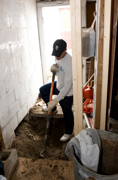 A.J. shovels dirt to work with the plumbing in the home.