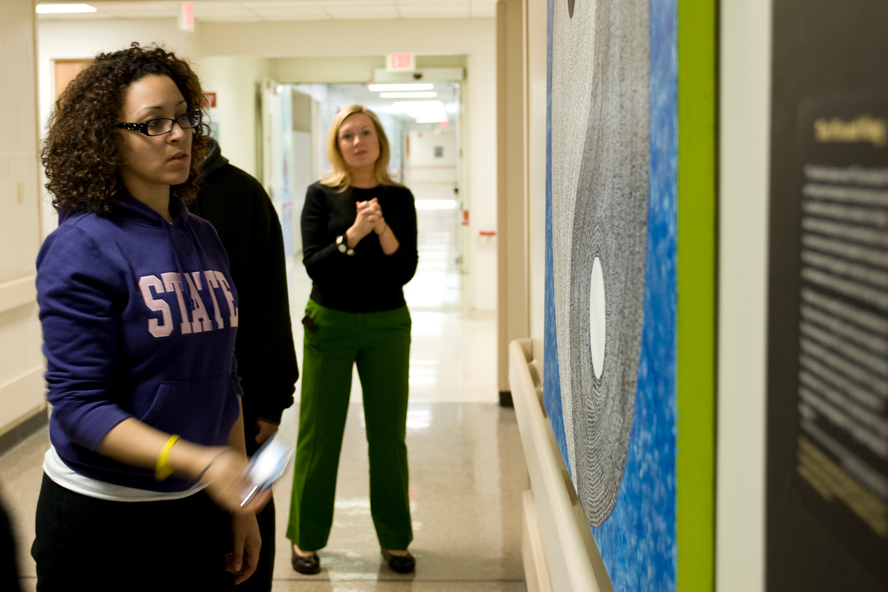 Students look at the artwork created by patients that fill a hall at St. Jude.