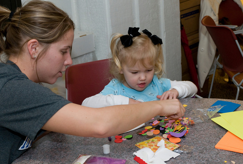 Anna McVay, junior, helps Madison Hurst, 2, with her book during the Build-A-Book exercise at the Scholastic Book Fair in the College of Education on Tuesday, January 29, 2008.