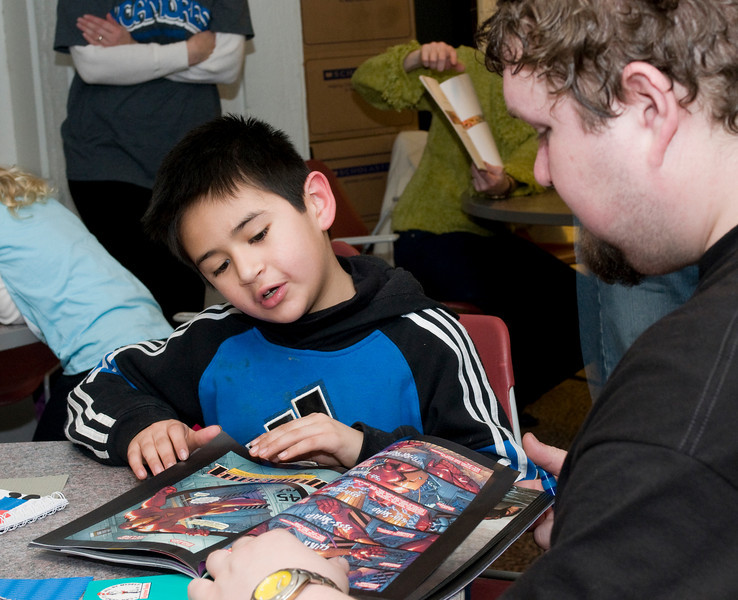 Matt Corey, junior, helps  Gustavo, 8, who attends second grade at Franklin Elementary,build a book as part of the Scholastic Book Fair in the College of Education on Tuesday, January 29, 2008.