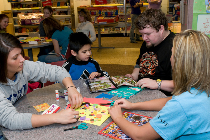 A group of students from Elementary Education class 335 help  Gustavo Jimenez, 8, who attends second grade at Franklin Elementary,build a book as part of the Scholastic Book Fair in the College of Education on Tuesday, January 29, 2008.