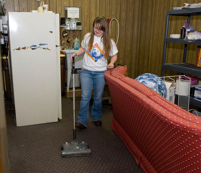April Elder, freshman, cleans the back room of the Children's Museum.