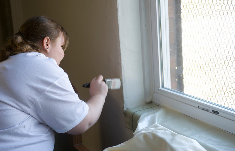 Sarah Rehfeldt, freshman, paints the window trim at the Community Center at 14th and Chestnut.