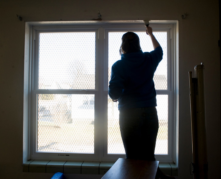 Abigail Miller, freshman, paints the window trim at the Community Center at 14th and Chestnut.
