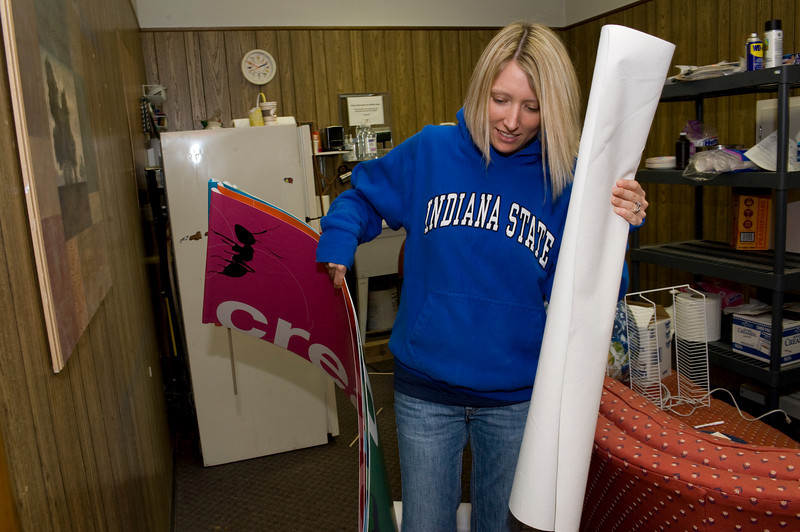 Scharlene Moore, sophomore, moves signs from the back room of the Children's Museum.