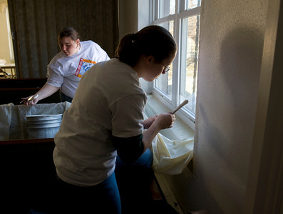 Sarah Rehfeldt, freshman, and Caitlin McCullough, freshman, paint the window trim at the Community Center at 14th and Chestnut.