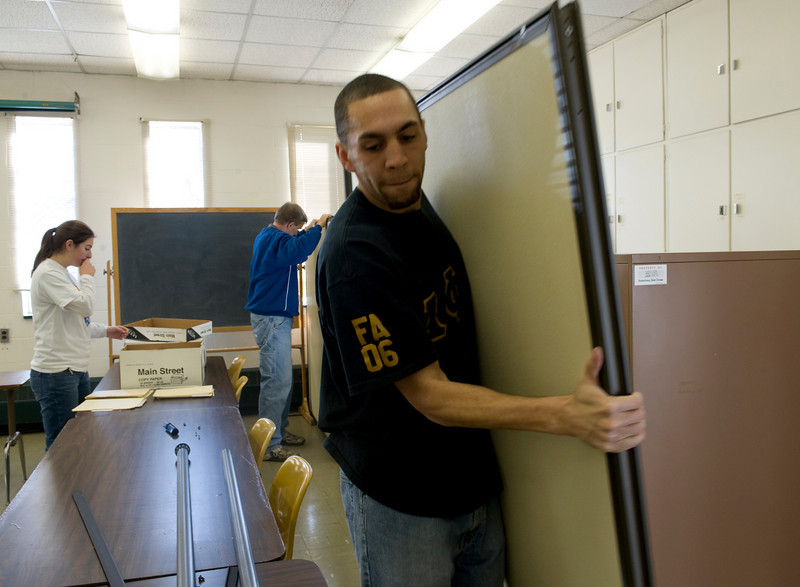 Rylen Peterson, grad student, moves office equipment at the Red Cross while volunteering for his fraternity, Alpha Phi Alpha.