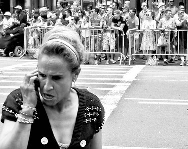 """Mother's love on the line.  Through the cheerful din of the crowd gathered at New York City's Gay Pride Parade, a mother proclaims angrily at the top of her lungs over her cell phone, """"I'm here to support my son!"""""""