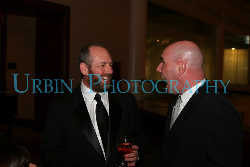 Two fellows chatting at a Wedding.