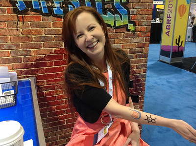 "ABRF Executive Director, Crystal Davis, is all smiles after receiving two tattoos at the ""FASEB Ink' tattoo booth."