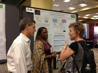 Dr. Michael Summers of the University of Maryland Baltimore County participates in the discussion of his PhD student's (Ms. Lola Brown) poster presentation during the 26th Annual Symposium of The Protein Society in San Diego.