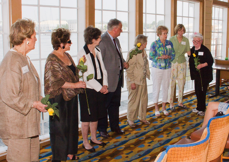 New Board members for the coming season are presented long-stemmed yellow roses by Judi