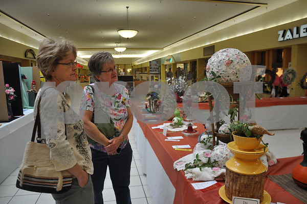 Kathy Meinders, left, and Bev Longnecker look over Chris Fulker's second-place winning entry in the Artistic Crafts section.