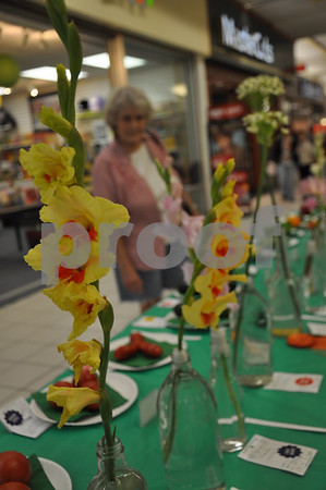 Hilda Sandven looks over the flowers and vegetables on display at the flower show on Saturday. These yellow flowers are third and second place winning Gladiolas by Judith Walrod and Frances Stetson