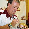 Coach Jimbo Fisher signs a helmet for a fan during FSU Fan Day held on August 14th at the Civic Center.