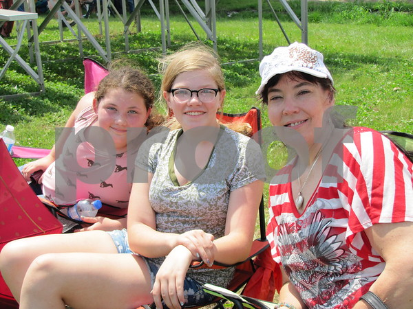 Mariah Mabe, Carlie Shing-hon, and Melissa Mabe were watching the barrel racing at the outdoor arena.