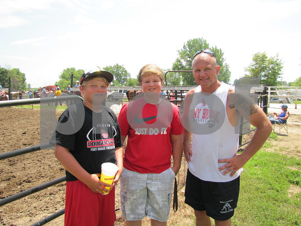 Cade Hovey, Colton Sortedahl, and Kit Hovey were watching the barrel racing at the outdoor arena.