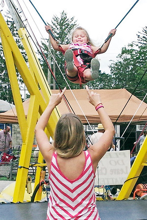 Mark Maynard | for The Herald Bulletin<br /> Cara Sherman, four, of Avon gets some coaching on the finer points of bungee bouncing from her mother, Bethany, on Saturday at the Lapel Village Fair.