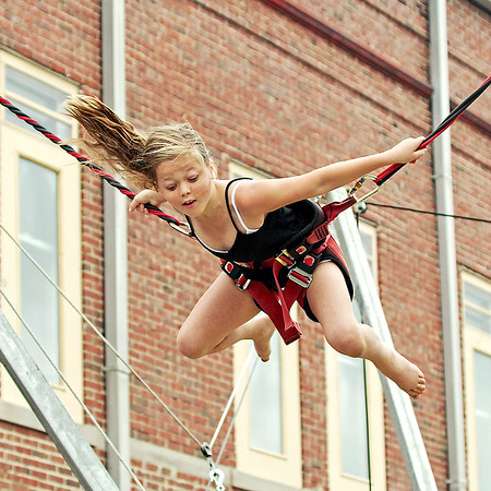 Mark Maynard | for The Herald Bulletin<br /> Nine-year old Emma Tomlinson of Lapel performs a mid-air somersault on the bungee cords at her hometown's Village Fair on Saturday.