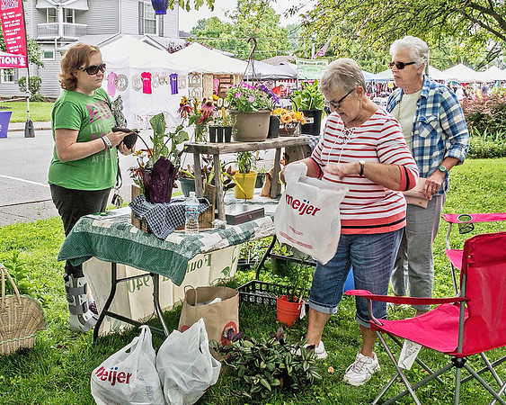 Mark Maynard | for The Herald Bulletin<br /> Amber Hensley purchases some plants from Karen Kilburn and Barbara Mitchel at the Rural Garden Club of Lapel's booth on Saturday during the Lapel Village Fair.