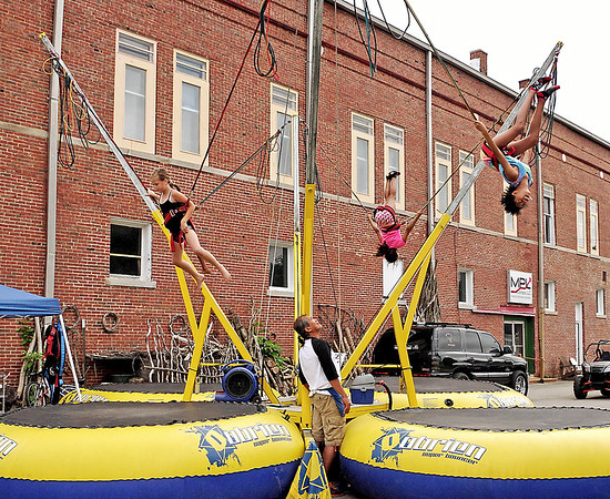 Mark Maynard | for The Herald Bulletin<br /> Emma Tomlinson, Contessa Onato and Dezire Smith fly high on the bungee cords at the Lapel Village Fair.