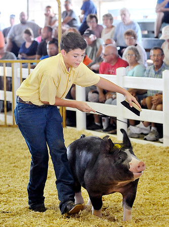 John P. Cleary | The Herald Bulletin<br /> Chandler Lowes keeps his Berkshire Barrow moving around the show ring during judging of the Berkshire Barrow classes. Lowes won first place in his weight class and then was judged overall champion of the Berkshire Barrow classes Monday.