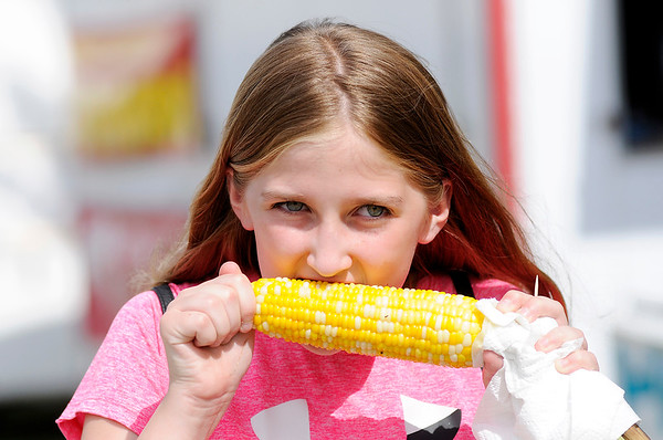 Don Knight | The Herald Bulletin<br /> Sydney Thompson, 12, enjoys an ear of grilled sweet corn from Ousley's during the Madison County 4-H Fair on Tuesday.