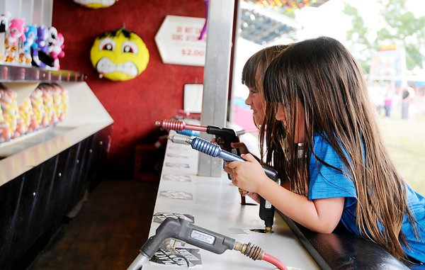 Don Knight | The Herald Bulletin<br /> Twin sisters Ember, foreground, and Emarie Shirley compete against each other on a midway game at the Madison County 4-H Fair on Tuesday.