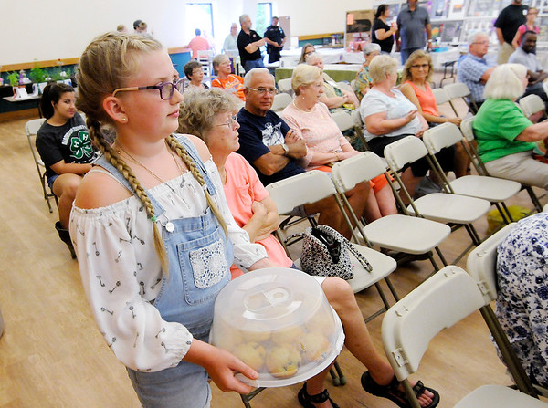 Don Knight   The Herald Bulletin<br /> Gwyn Key, 10, auctions her blue ribbon blue berry muffins during the Extension Homemakers Auction at the Madison County 4-H Fair on Tuesday.