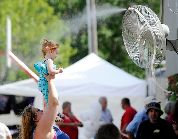 Don Knight | The Herald Bulletin<br /> Layla Welsh cools off under a misting fan with some help from her aunt Brandy Welsh during the Madison County 4-H Fair on Tuesday.