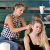 John P. Cleary | The Herald Bulletin<br /> During a break in the sheep judging Wednesday at the 4-H Fair, Chainey Lowe, 15, braids Caylene Cole's, 18, hair as they sit in the show arena. Both girls are from Frankton.