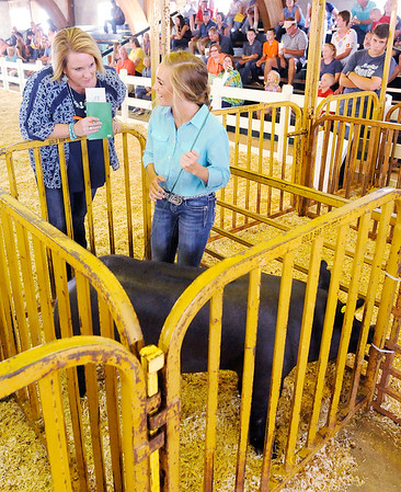 Don Knight | The Herald Bulletin<br /> Judge Tracie Egger asks Noelle Loller a question about swine during the supreme showmanship competition at the Madison County 4-H Fair on Thursday.