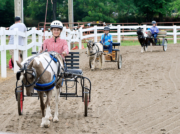 John P. Cleary   The Herald Bulletin<br /> Jessica Van Ness, foreground, Emily Van Ness, and Brianna Lane circle the ring as the compete in the 56 inches and under Pleasure Driving class at the 4-H Horse & Pony Show Friday.