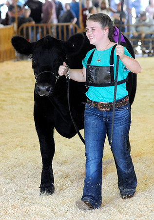 Don Knight | The Herald Bulletin<br /> Adaelyn Berg smiles as she leaves the show ring after winning the Champion County Raised Heifer Tuesday at the 4-H Fair.