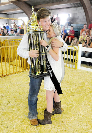 Don Knight | The Herald Bulletin<br /> 4-H Fair Queen Anahleisa Forrester gives Miller Smith the trophy and a hug after he won Supreme Showmanship on Thursday.