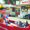 Alex Jenkins, 4, from Fishers, has a good spot to eat his ice cream bar as his dad pulls him along the Lapel Village Fair in his wagon.